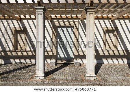 front view on the side entrance of an old villa with a pergola. The strong sunlight throws dark shade stripes on the building.