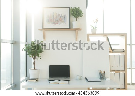 Front view picture of studio workplace with blank notebook, laptop. Designer comfortable work table, home office. - stock photo