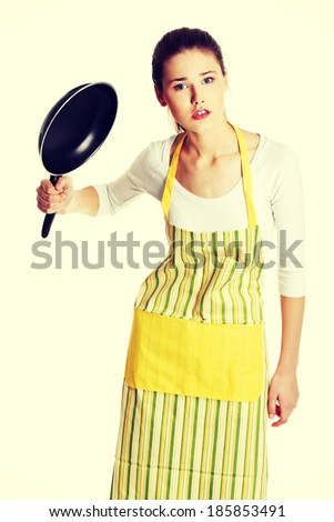 Front view portrait of a young angry caucasian female teen dressed in apron, trying to hit with a frying pan