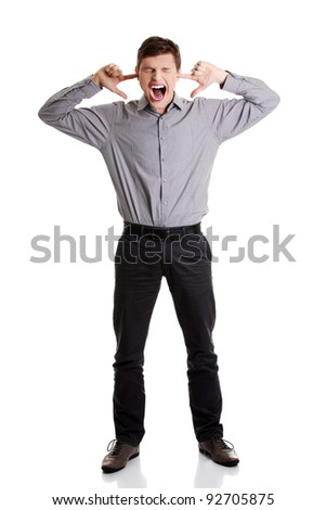 Front view portrait of a young angry man plugging his ears and shouting, on