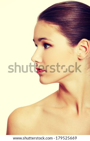 Front view portrait of a young beautiful female caucasian teen having naked arms, looking to the site