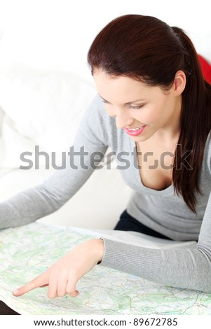 Front view portrait of a young beautiful woman, sitting on a couch at home and having a look at a map. - stock photo