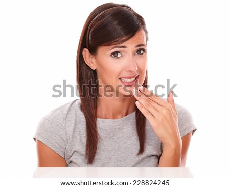 Front view portrait of beautiful hispanic woman with wrong gesture looking at camera on isolated studio - stock photo