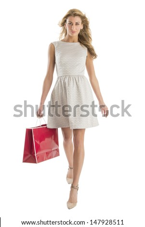 Front view portrait of young woman walking with shopping bag isolated over white background - stock photo