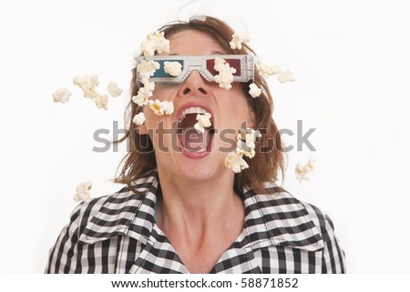 Front view portrait of young woman with 3D glasses and popcorn in the air - stock photo