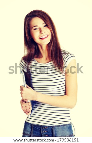 Front view portrait young happy female caucasian student holding a notebook - stock photo