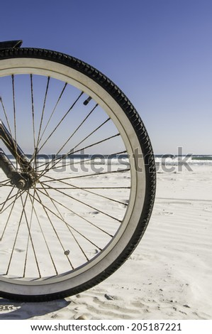 Front wheel of bicycle on sandy, sunny beach in Florida - stock photo