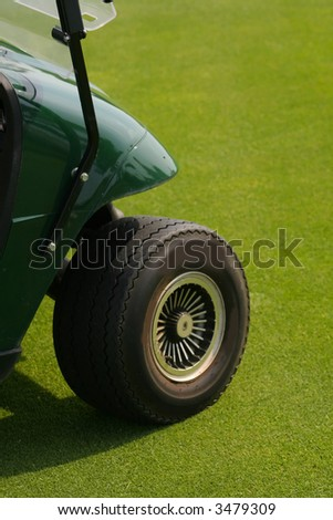 Front wheel of golf cart on lawn - stock photo