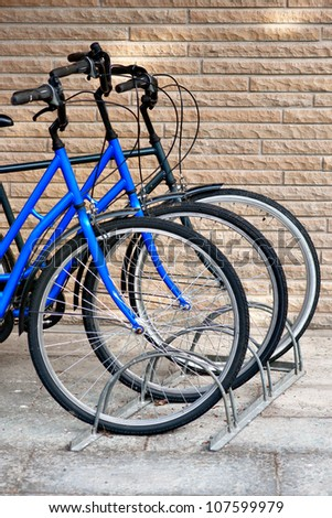 Front wheels of three bicycles in bicycle stand. Focus on middle bike.