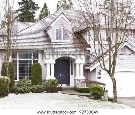 Front yard with light snow, bare trees, evergreens and front of home - stock photo