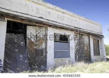 Frontal, angled view of an old, abandoned garage with large wooden doors