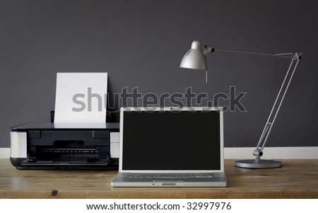 frontal Home office desk with laptop and printer - stock photo
