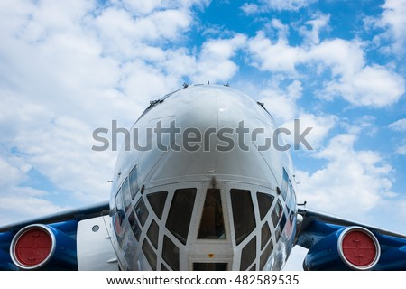 Frontal partial view of a modern heavy transport aircraft against the background of blue sky and white clouds