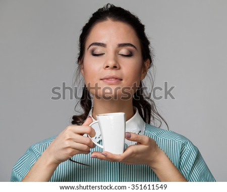Frontal  portrait of an attractive brunette with a cup of coffee,eyes are closed in pleasure, the mouth is slightly open, the chin is elevated,  gray background