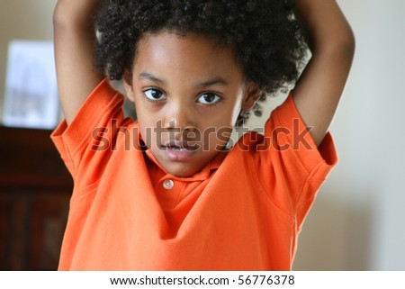 Frontal shot of a young boy looking happy with arms up wearing an orange golf shirt. - stock photo