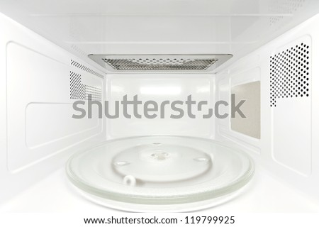 Frontal view inside white, empty clean microwave oven interior - stock photo