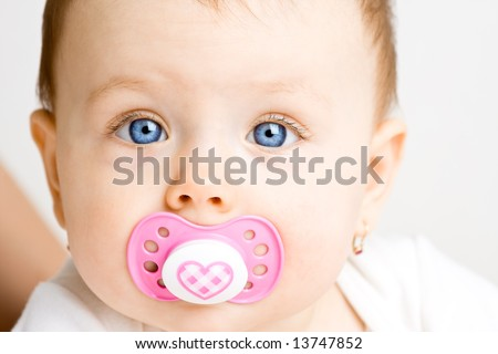 Frontal view of a cute baby girl with a soother in her mouth - stock photo