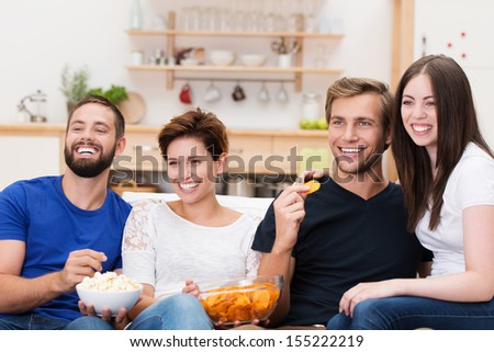 Frontal view of a laughing group of diverse young friends sitting on a sofa watching television and eating snacks - stock photo