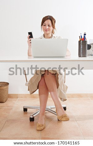Frontal view of a young and attractive professional businesswoman sitting at her work desk against a white wall and using a laptop computer and a telephone to make a call in her office, interior. - stock photo