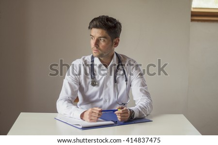 Frontal view of a young doctor looking to the side. He is sitting at the desk wearing a stethoscope around his neck, has an open notebook and is holding a pen with hands while while he is thoughtful. - stock photo