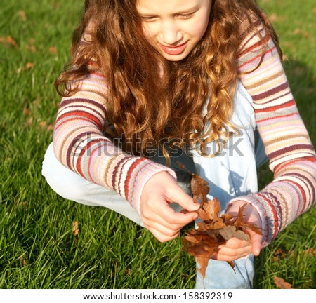Frontal view of a young hispanic child girl crouching and collecting autumn dry leaves from the green grass ground in a park during a sunny and warm fall day, outdoors. - stock photo