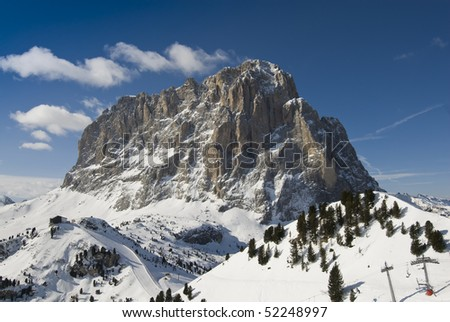 "Frontal view of the ""Sassolungo"" mountain peak in winter with blue sky. Val Gardena, Dolomites, Italy. - stock photo"