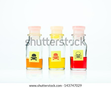 frontal view of three transparent colorless bottles filled with orange, yellow and red liquid and marked as poisonous on a white background - stock photo