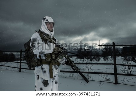 Frontier guard. Military near the fence with barbed wire. soldier against the background of a winter landscape. - stock photo