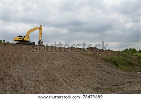 Frontloader strips all the vegetation off the side of a hill - stock photo