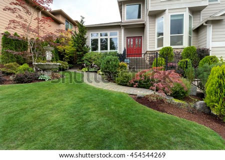 Frontyard garden of house with water fountain green grass lawn paver brick path trees and shrubs landscaping - stock photo