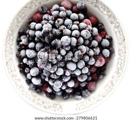 Frosen cranberries and black currant berries in white bowl isolated - stock photo