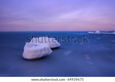 Frost and the sea are made of stone icebergs that futuristic look against the backdrop of sliding beneath the waves. The photo was taken at long exposures. - stock photo
