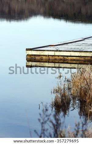 frost covered dock at shoreline in autumn - stock photo