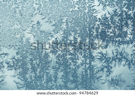 Frost design found early in the morning on a drivers side car window looks like a whimsical frosty forest scene.  It appears that nature likes to reuse it's most successful designs in various ways. - stock photo
