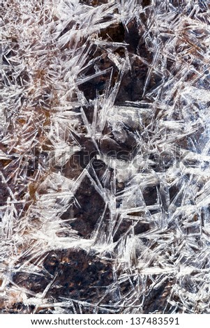 frost ice crystals under frozen water in spring forest - stock photo