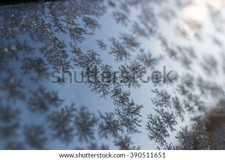 Frost patterns on a glass window creates winter themed patterns with a blue wintry sky background. - stock photo