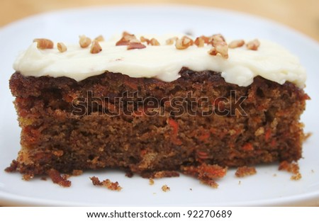 Frosted Carrot Cake Slice on a White Plate - stock photo