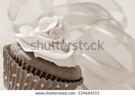 Frosted cupcake in polka dot wrapper with swirls of  chiffon ribbon as background. Macro with shallow dof in sepia tones for nostalgic effect. - stock photo