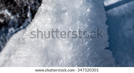 Frosted flakes - Snow flakes covered in large frost crystals. Fresh fallen snow, further covered by layers of frost, manifesting from the warmer water's rising mist nearby. - stock photo