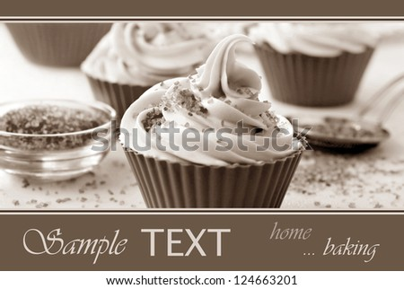 Frosted homemade cupcakes being decorated with sugar sprinkles.  Still life in sepia tones for nostalgic effect.  Macro with extremely shallow dof. - stock photo