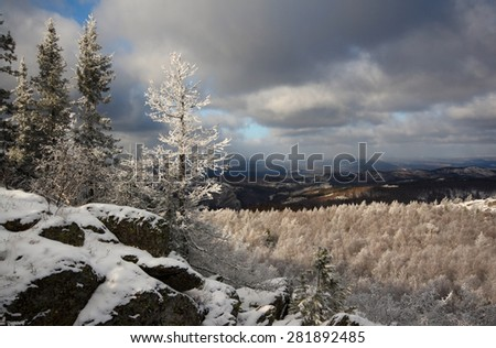 Frosted larch, growing among the rocks covered with newly fallen snow, sparkles in the sun on the background of birch forest  and dramatic sky with heavy clouds, Sunduk mount, Southern Urals, Russia.  - stock photo