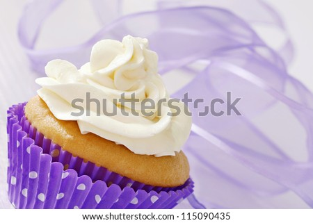 Frosted vanilla cupcake in polka dot wrapper with swirls of lavender chiffon ribbon as background.  Macro with shallow dof. - stock photo