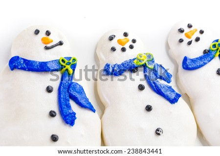 Frosted white sugar cookies in shape of snowman.