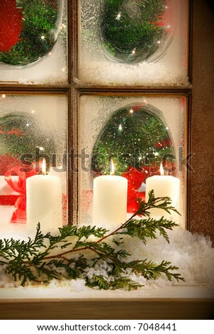 Frosted window looking into festive candles and holiday decorations - stock photo