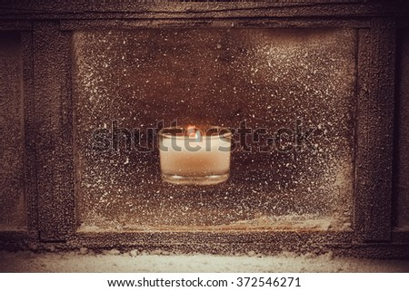 Frosted winter window. One light candle  - stock photo