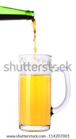 Frosty beer pouring from bottle in to the glass isolated  on a white background - stock photo