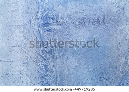 Frosty blue patterns on glass. Horizontal orientation of a shot, light strip at the left - stock photo