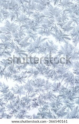 frosty christmas pattern on frozen winter window glass - stock photo