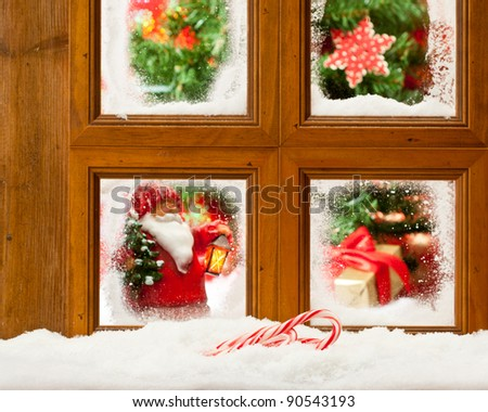Frosty Christmas window with focus on candy canes in the snow - stock photo