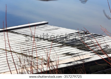 frosty dock in cold blue water along shoreline closeup - stock photo